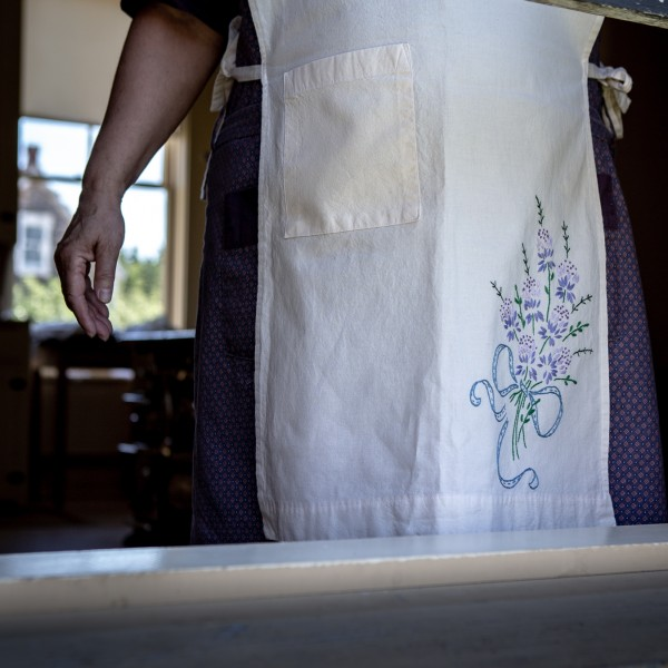 An embroidered apron, created by the Village's 20th-century section seamstresses