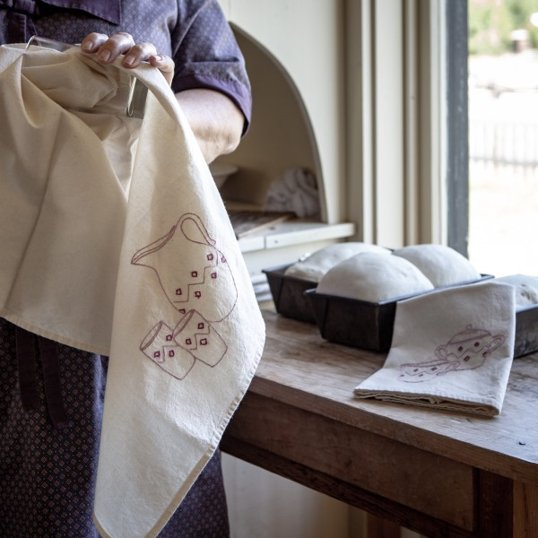 An embroidered cotton dish towel, created by the Village's 20th-century section seamstresses